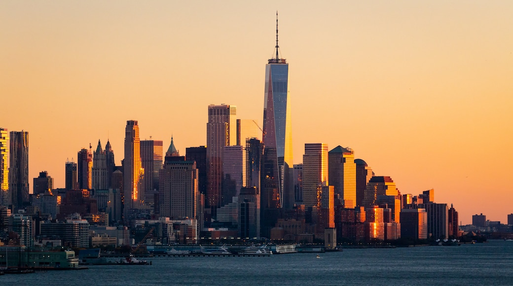 Lower Manhattan showing a bay or harbor, a sunset and a city