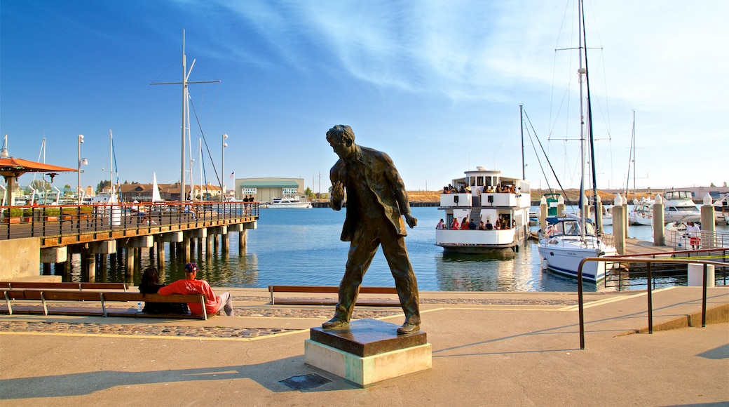 Jack London Square which includes a bay or harbor and a statue or sculpture