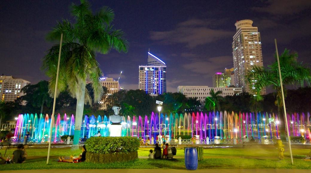 Rizal Park showing a skyscraper, night scenes and a garden