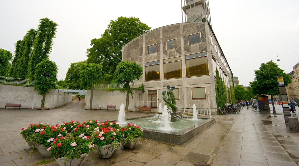 Aarhus Rådhus som viser gadeliv, blomster og et springvand