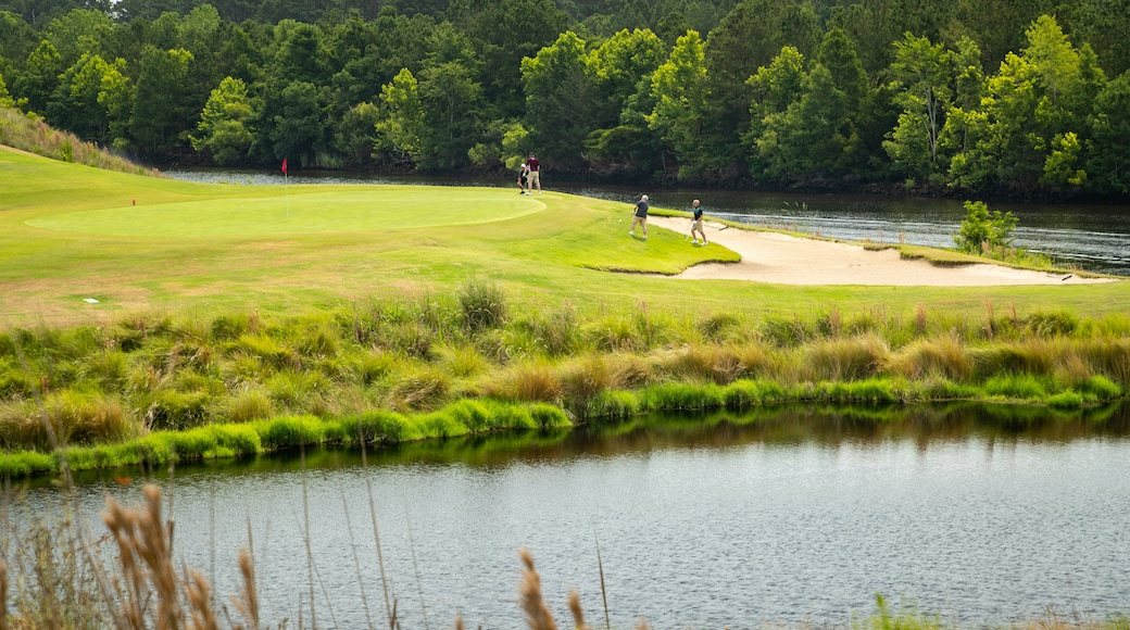 Grand Dunes Golf Course which includes golf and a pond as well as a small group of people