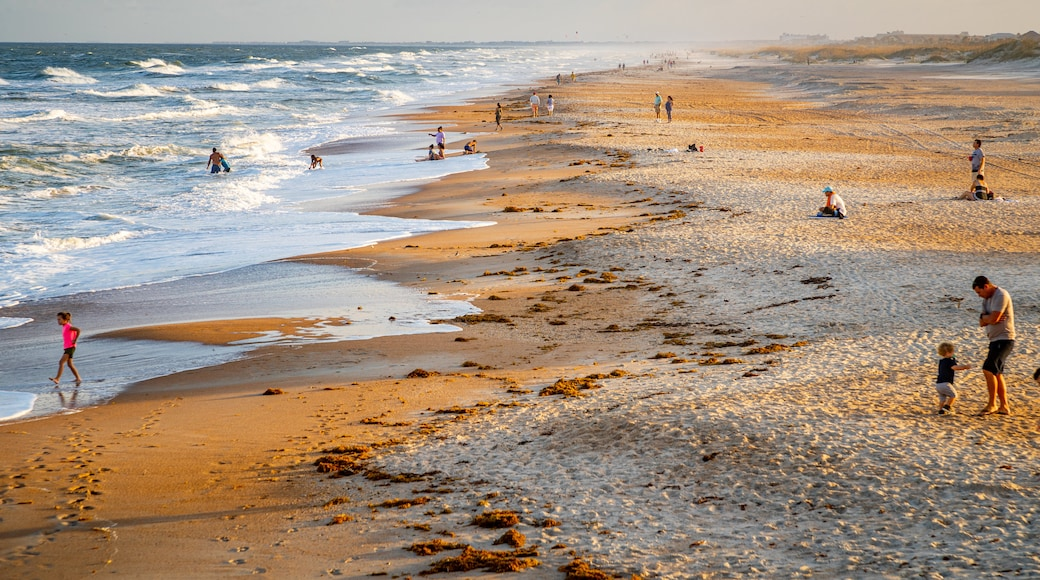 St. Augustine Beach showing a sandy beach and general coastal views as well as a family