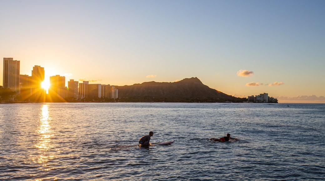 Waikiki showing surfing, a sunset and general coastal views