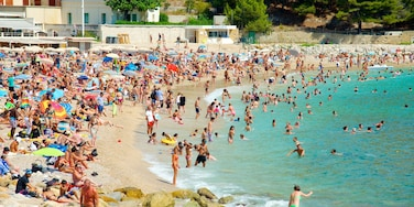 Cassis showing swimming and a sandy beach as well as a large group of people