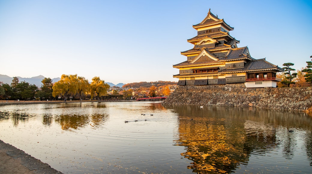 Matsumoto Castle featuring a pond, heritage architecture and a sunset