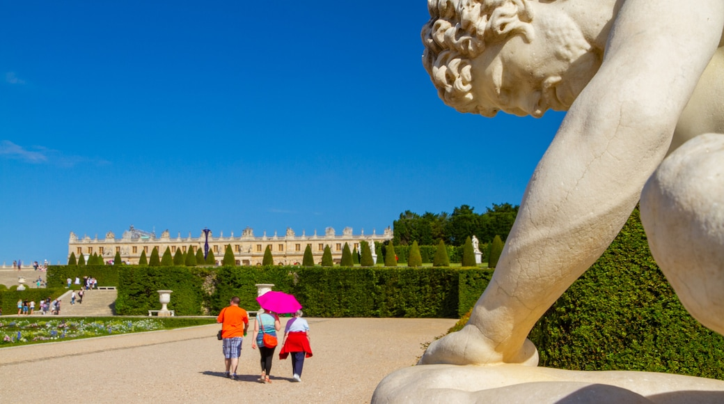 Versailles showing a garden and a statue or sculpture as well as a small group of people