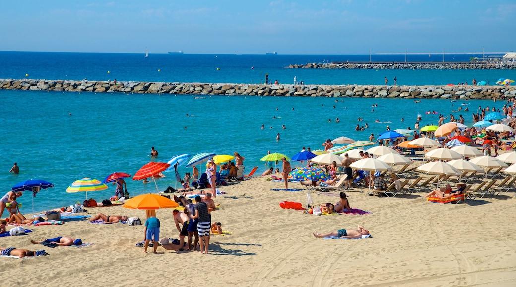 Barcelona mostrando una playa de arena y natación y también un grupo grande de personas