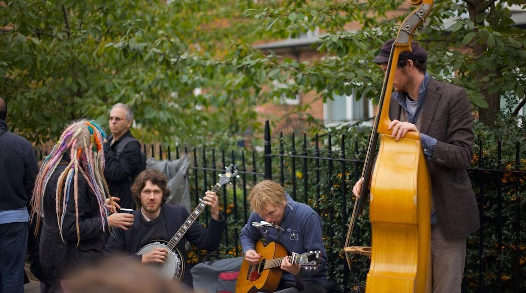 Notting Hill toont straatoptredens en een park en ook een klein groepje mensen