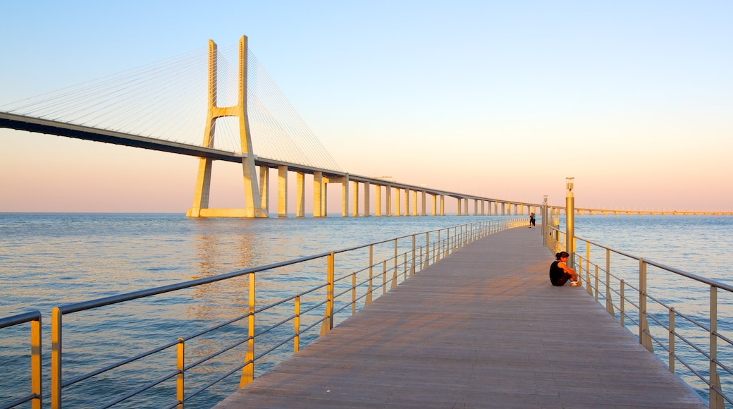 Vasco da Gama Bridge featuring a sunset, modern architecture and a bay or harbour