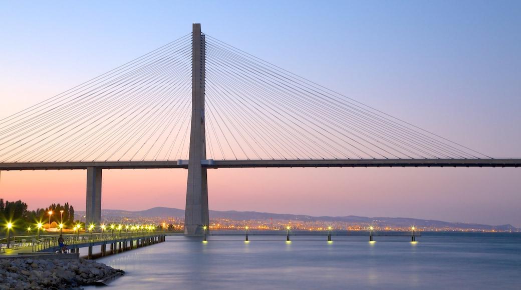 Vasco da Gama Bridge which includes a bridge, modern architecture and a sunset