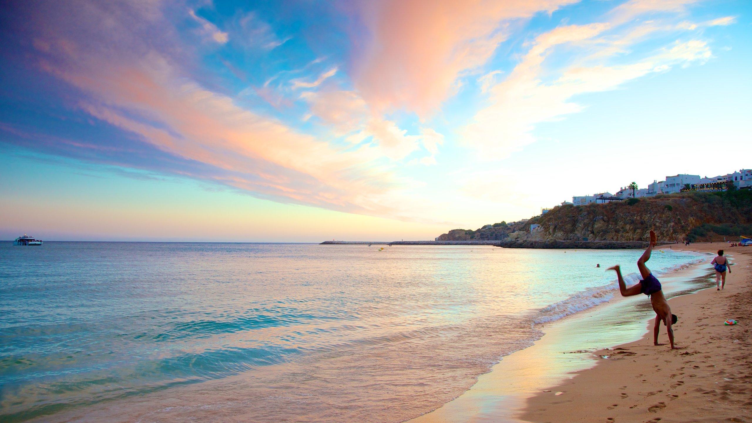 Albufeira mostrando paisagem e uma praia de areia assim como um homem sozinho