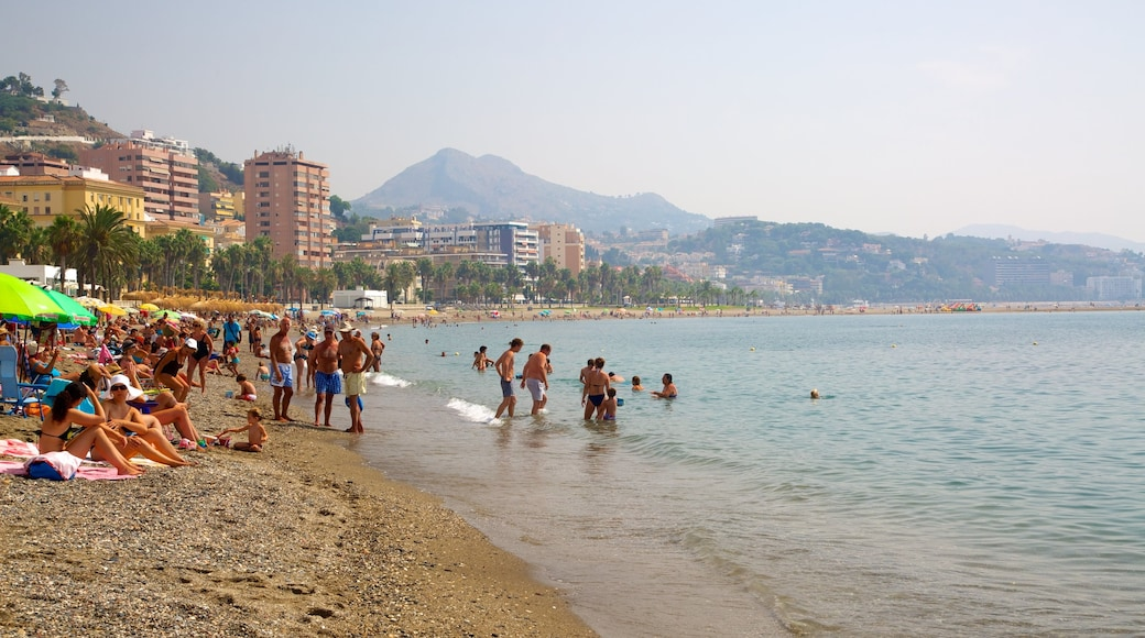 Playa de la Malagueta som visar bad, en sandstrand och en kuststad