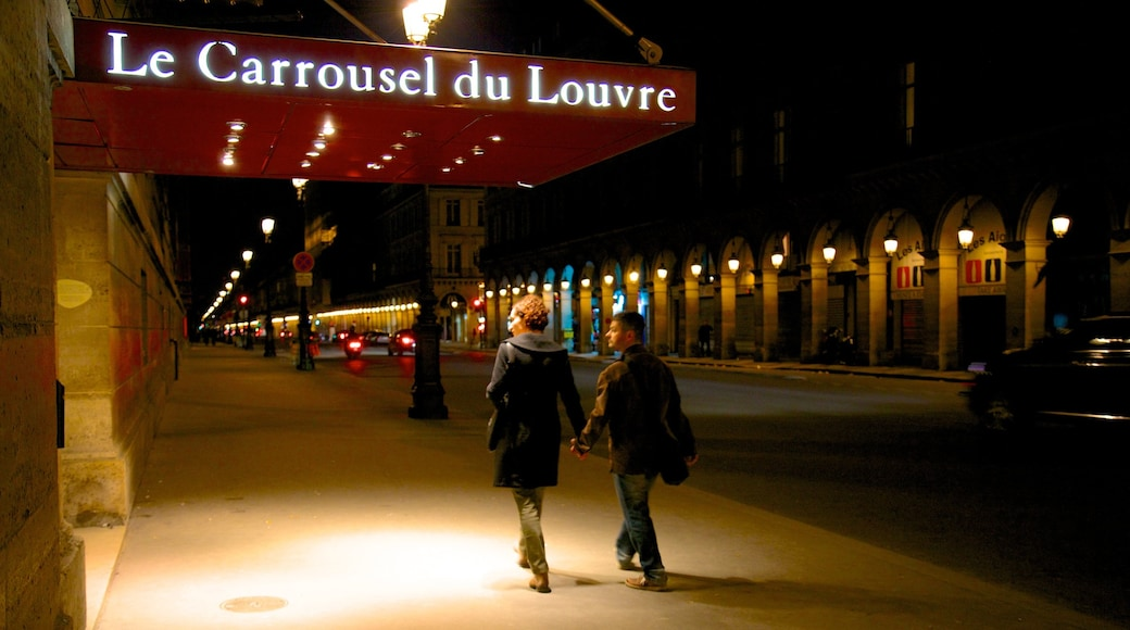 Louvre Museum featuring night scenes, street scenes and signage