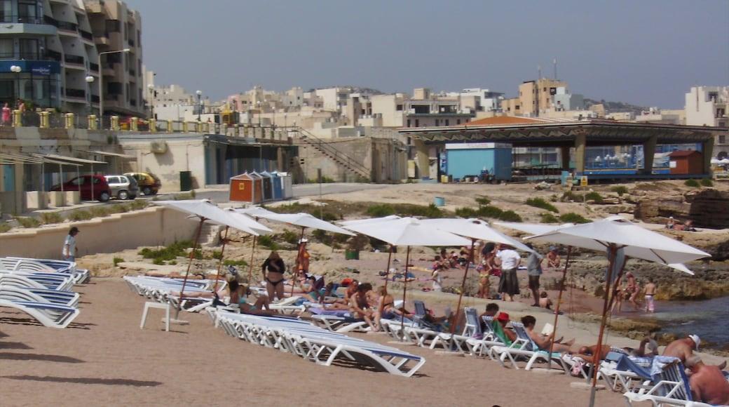 Bugibba welches beinhaltet Strand und Küstenort sowie große Menschengruppe