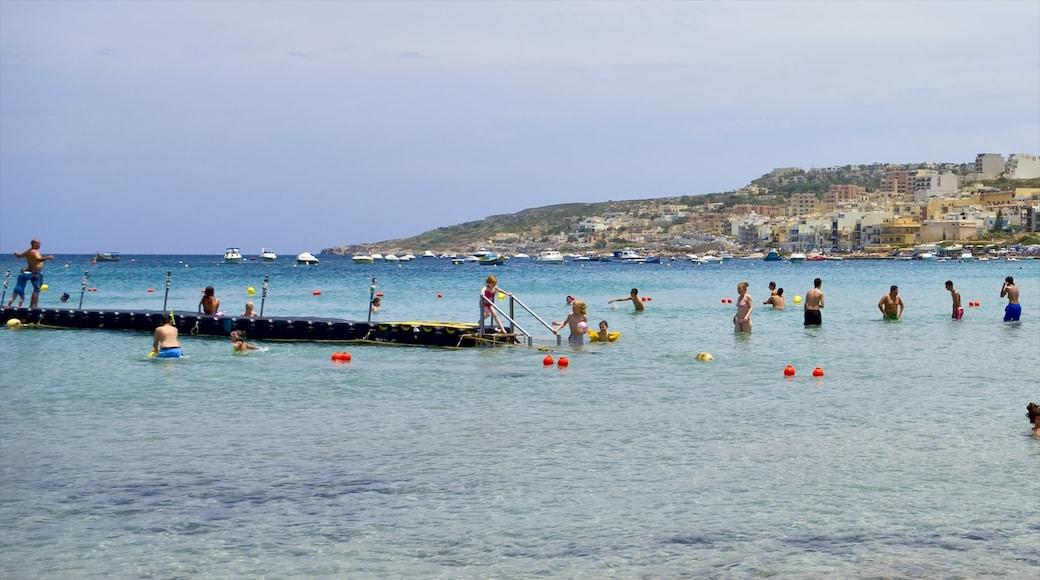 Mellieħa mettant en vedette baignade et vues littorales aussi bien que important groupe de personnes