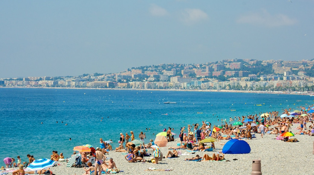 Nice which includes a sandy beach and a coastal town as well as a large group of people