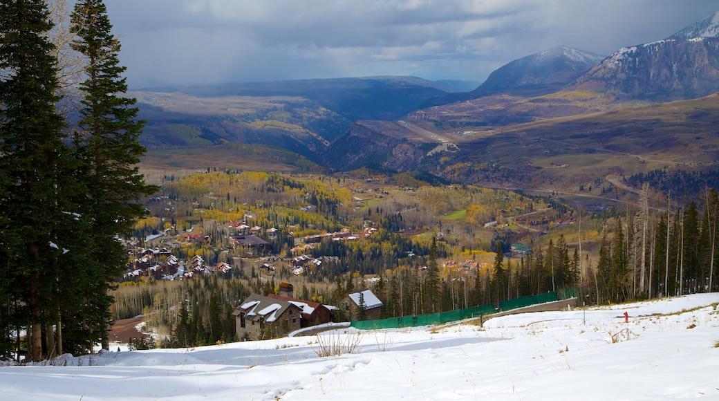Telluride Ski Resort mostrando montañas, nieve y una pequeña ciudad o aldea