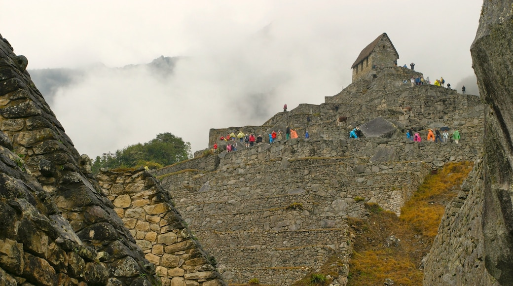 Machu Picchu which includes hiking or walking, a ruin and mist or fog
