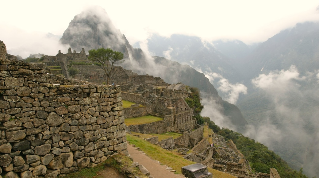 Machu Picchu which includes building ruins, mist or fog and mountains