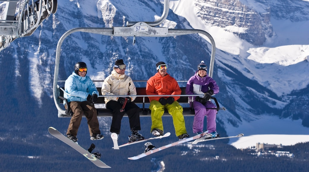 Lake Louise Mountain Resort showing snow and a gondola as well as a small group of people