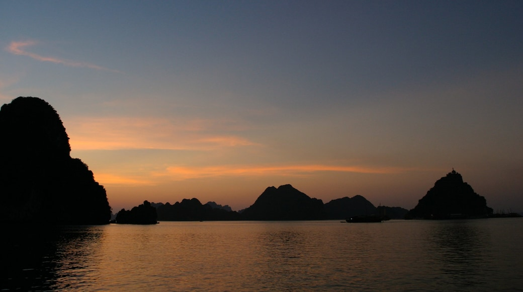 Halong Bay which includes a bay or harbour, a sunset and landscape views