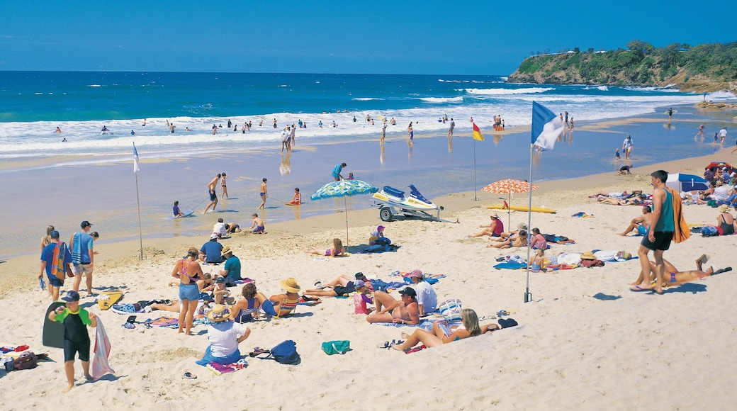 Coolum Beach which includes swimming and a sandy beach as well as a large group of people