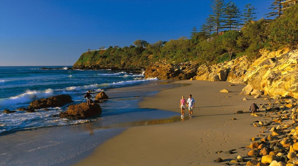 Coolum Beach featuring a sandy beach and rocky coastline as well as a couple