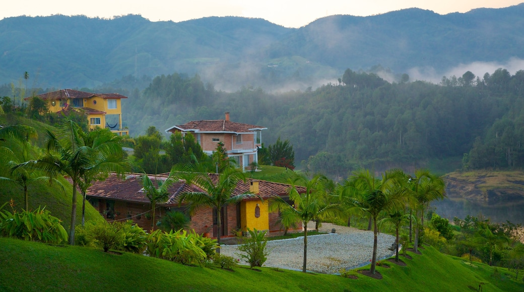 Rock of Guatape featuring a house, mist or fog and tranquil scenes