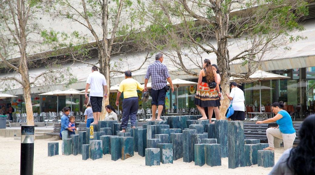 Parc Pies Descalzos montrant jardin et aire de jeu aussi bien que petit groupe de personnes