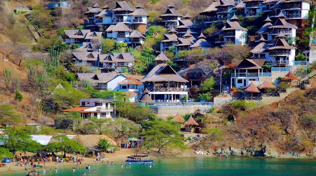 Taganga Beach which includes a sandy beach and a coastal town as well as a large group of people