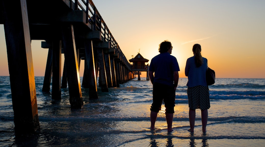 Naples Pier which includes a sandy beach, views and a sunset