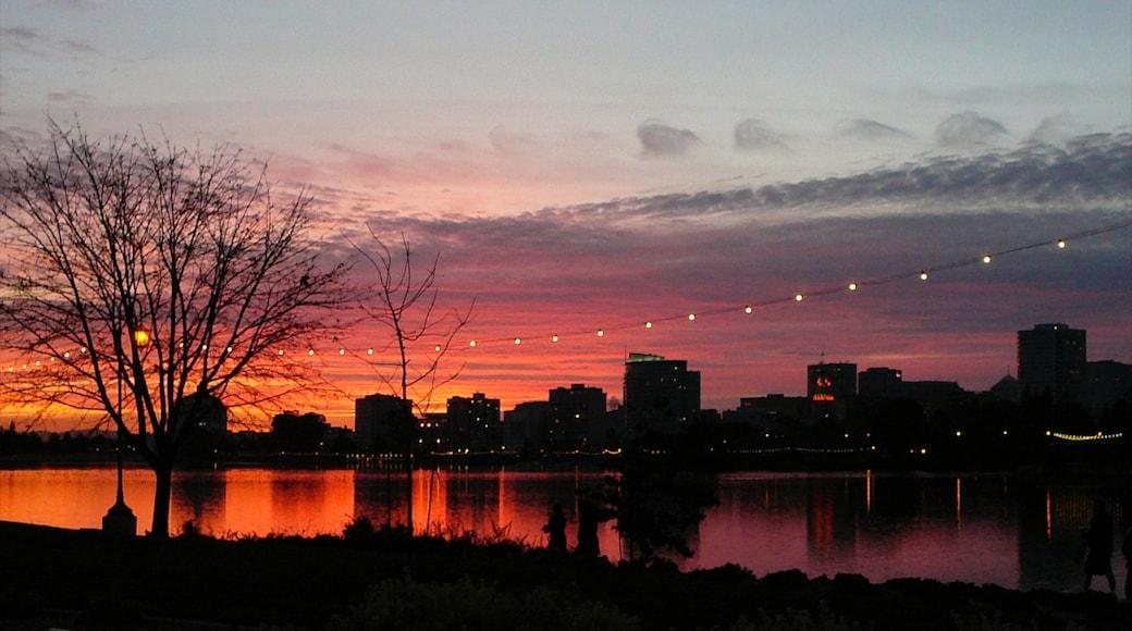Oakland som omfatter en solnedgang, skyline og en sø eller et vandhul