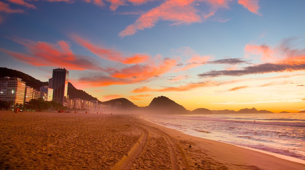 Playa de Copacabana que incluye un atardecer, una playa de arena y vista general a la costa