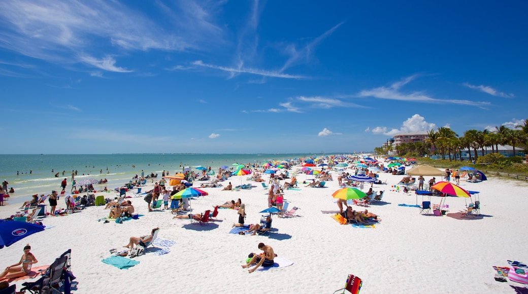 Fort Myers Beach showing a sandy beach as well as a large group of people