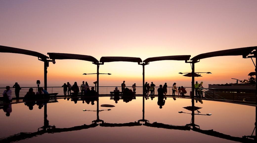 Lima que incluye una puesta de sol y un estanque y también un gran grupo de personas