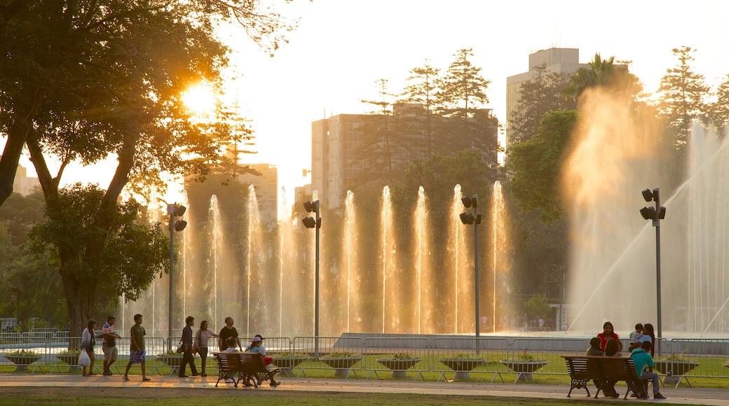 Parque da Exposição caracterizando uma fonte e um jardim assim como um grande grupo de pessoas