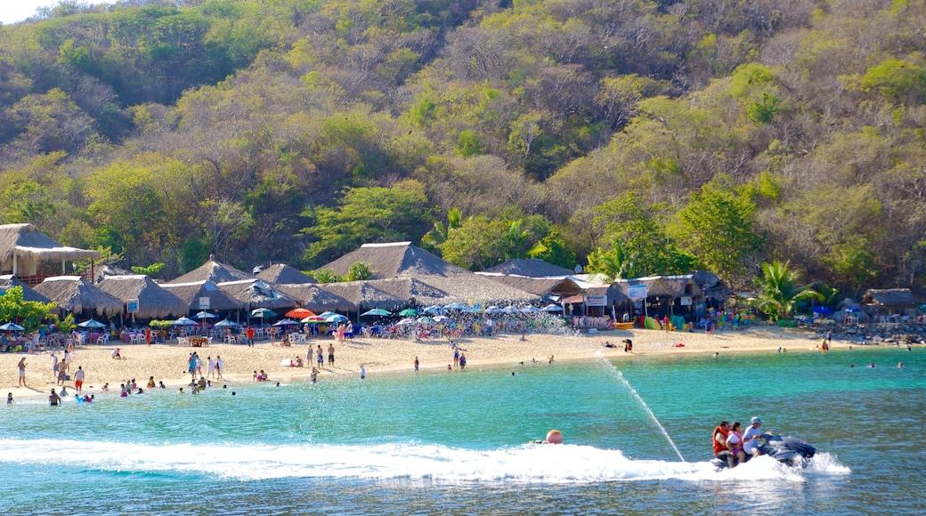Playa La Entrega ofreciendo una playa de arena, una ciudad costera y jet ski