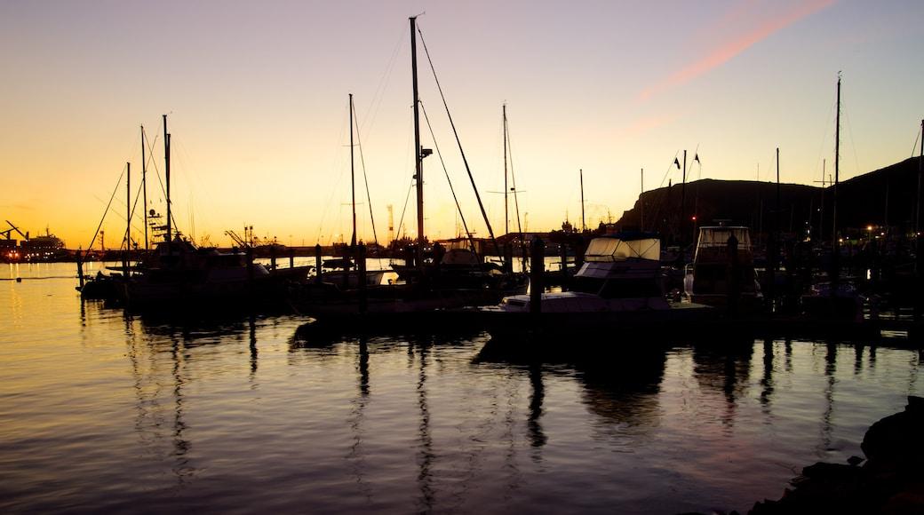 Ensenada ofreciendo paseos en lancha, una bahía o puerto y una puesta de sol