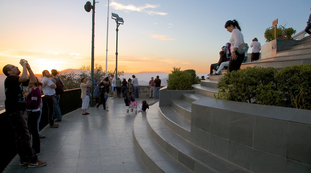 San Cristobal Hill featuring a sunset and views as well as a large group of people