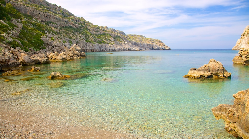 Anthony Quinn Bay featuring a pebble beach, rugged coastline and a bay or harbour
