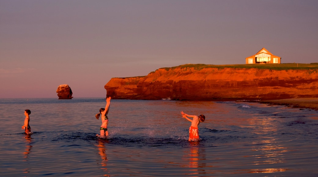 Prince Edward Island showing swimming, rocky coastline and a sunset
