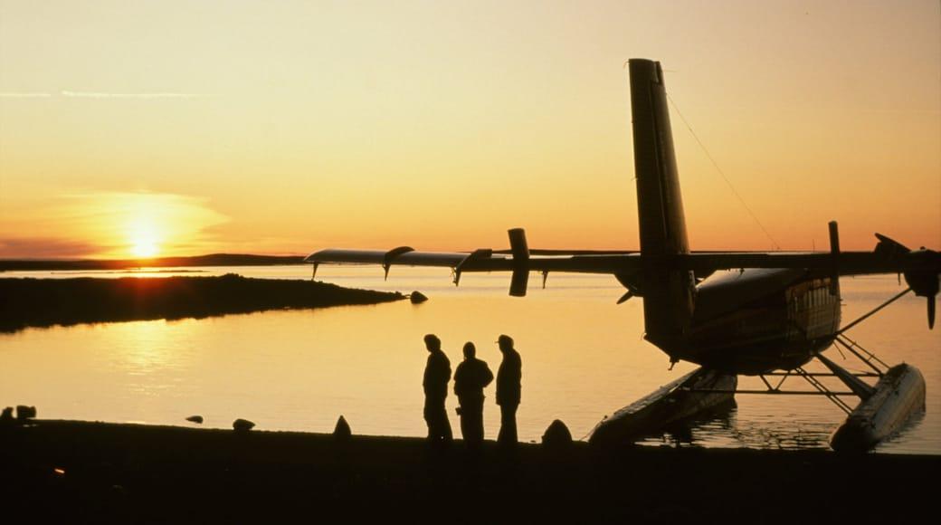 Nunavut que incluye aeronave y una puesta de sol y también un pequeño grupo de personas