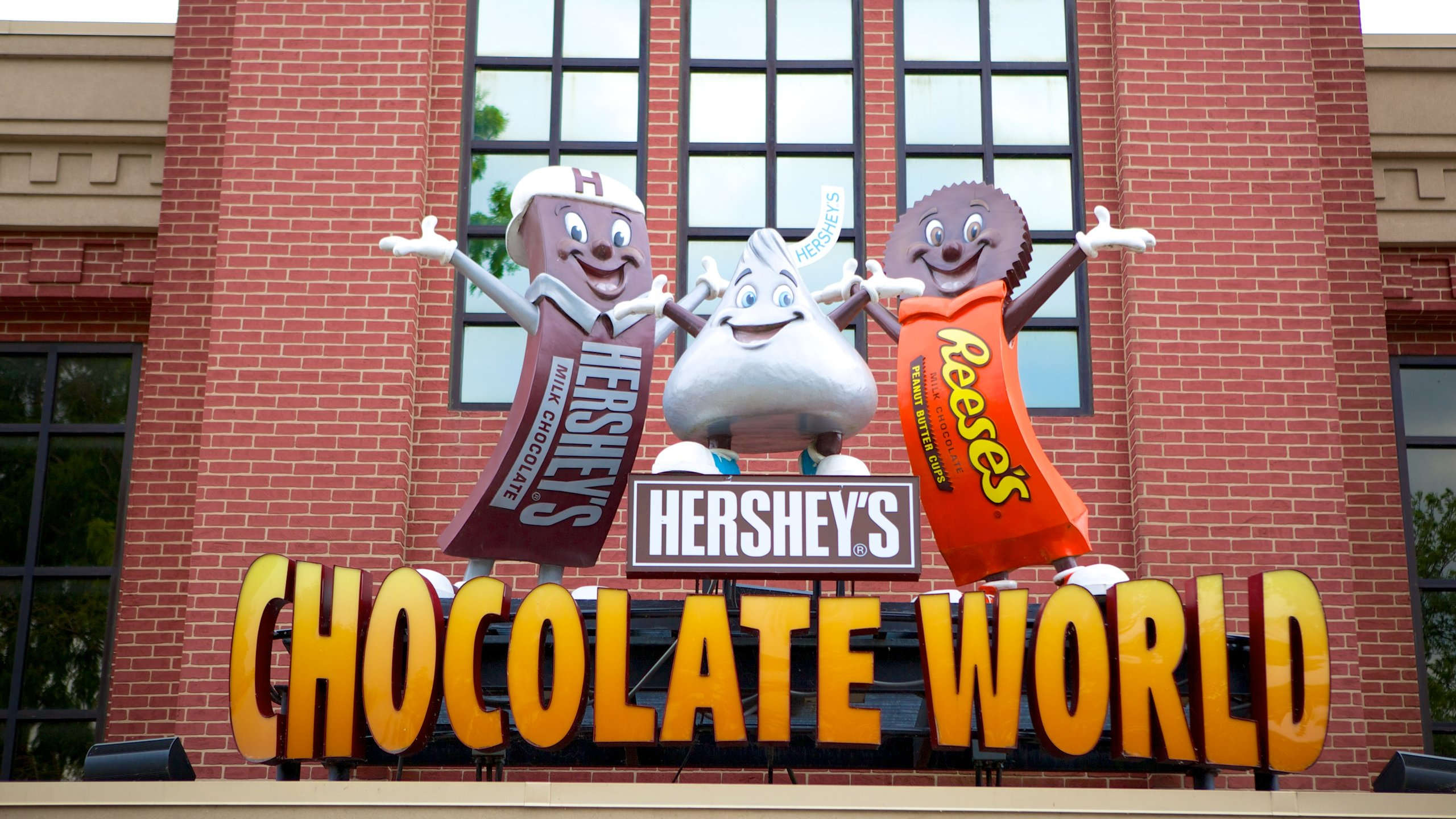 """Sign at Hershey's Chocolate World that has the Hershey Bar, Kiss, and Reeses Cup characters standing on top of the words """"Hershey's Chocolate World"""""""