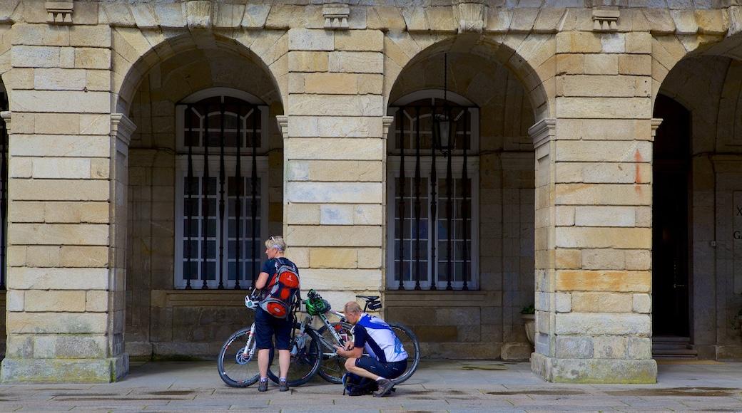 Plaza del Obradoiro mostrando ciclismo y escenas cotidianas y también una pareja