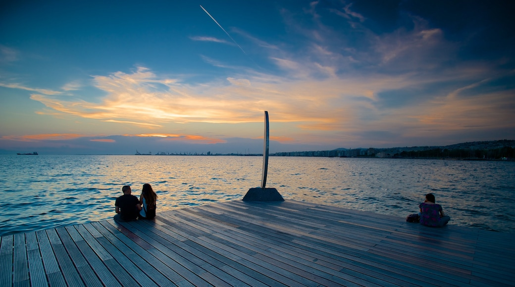 Thessaloniki showing a sunset and general coastal views as well as a small group of people
