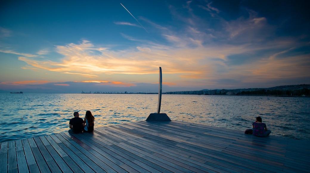 Thessaloniki welches beinhaltet allgemeine Küstenansicht und Sonnenuntergang sowie kleine Menschengruppe
