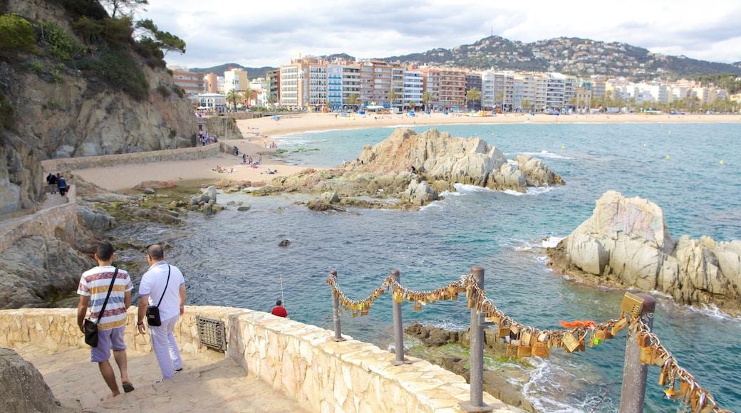 Lloret de Mar Strand welches beinhaltet Felsküste und Stadt sowie kleine Menschengruppe