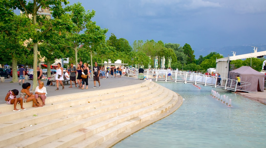 Lausanne showing a square or plaza and a pond as well as a large group of people