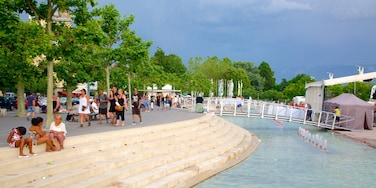 Lausanne featuring a square or plaza and a pond as well as a large group of people
