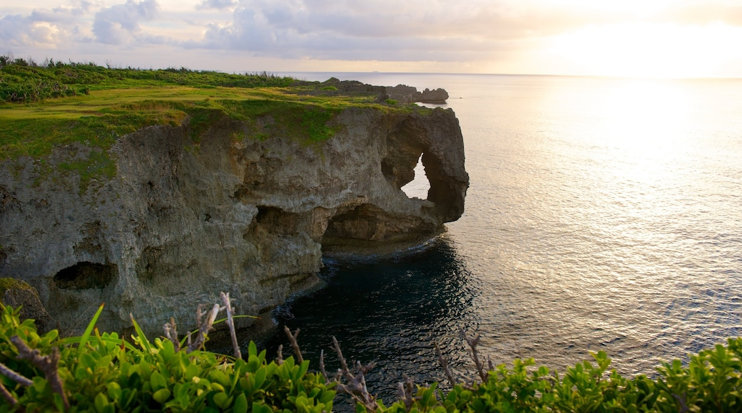 Cape Manza which includes rugged coastline and a sunset